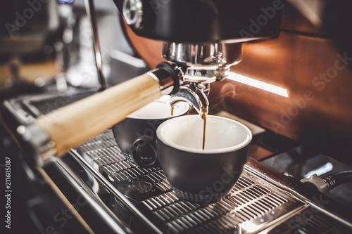 Leinwanddruck Bild Espresso poruing from coffee machine at cafe