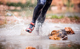 Dynamic run through river splashing water, cross country trail