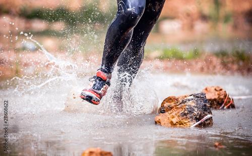 Fototapeta Dynamic run through river splashing water, cross country trail