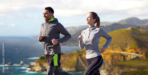 Wall mural fitness, sport, people and healthy lifestyle concept - happy couple running over bixby creek bridge on big sur coast of california background