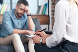 cropped image of female counselor writing in clipboard while depressed male patient sitting on sofa at office - 211614058