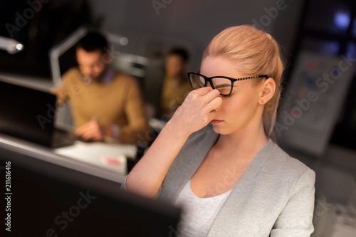 Wall mural business, overwork, deadline, vision and people concept - tired businesswoman with glasses working late at night office and rubbing eyes