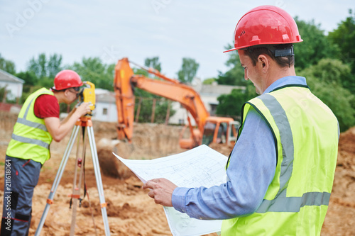 Construction workers on building area. Foreman with blueprint and surveyoor