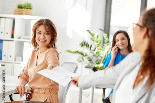 business and people concept - businesswomen giving each other papers at office