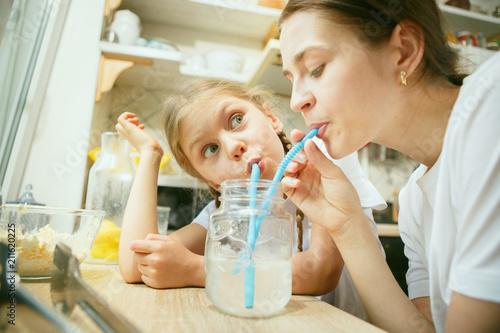 Leinwanddruck Bild The happy smiling caucasian family in the kitchen preparing breakfast