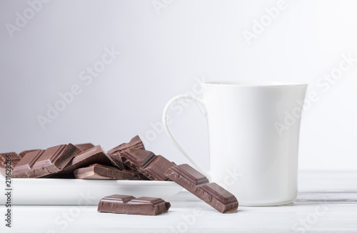 Canvas Chocolade White mug of hot drink and bitter chocolate pieces.