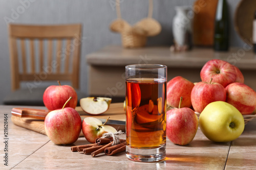 Fototapeta Glass of apple juice , apples and cinnamon sticks .
