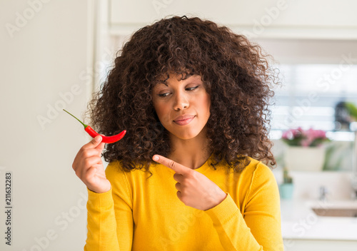 Leinwanddruck Bild African american woman eating red hot chili pepper very happy pointing with hand and finger