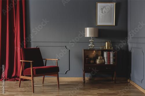 Prawdziwe zdjęcie rogu retro salonu z elegancką, beżową lampą na drewnianej szafce obok czerwonego fotela