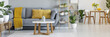 Leinwanddruck Bild - Real photo of a grey sofa with yellow pillows standing behind a table and next to a shelf with ornaments in living room interior with table and chairs in the bacground