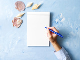 woman writes in notebook on stone blue table, Mock up with frame of seashell, top view, planning holiday by sea - 211637673