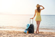 Leinwanddruck Bild - Beautiful young woman with a hat standing with suitcase on the wonderful sea background, concept of time to travel