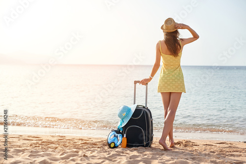 Leinwanddruck Bild Beautiful young woman with a hat standing with suitcase on the wonderful sea background, concept of time to travel