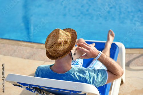 Leinwanddruck Bild Man using mobile phone on vacation by the pool in hotel, concept of a freelancer working for himself on vacation and travel