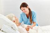 Altenpflegerin betreut kranke Seniorin - 211647213