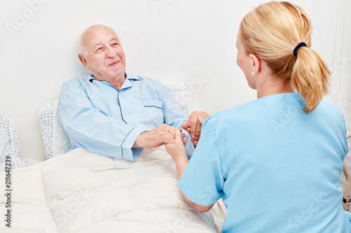 Leinwanddruck Bild Krankenschwester hält Hände von einem Senior