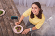 Organic salt. Top view of cheerful teen blogger smiling to camera while preparing salad