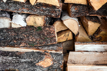 Firewood in woodpile.Fresh birch and pine logs covered with snow in winter.