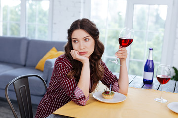 Nice hairstyle. Appealing stressed woman with nice hairstyle drinking glass of red wine on her own © Viacheslav Iakobchuk