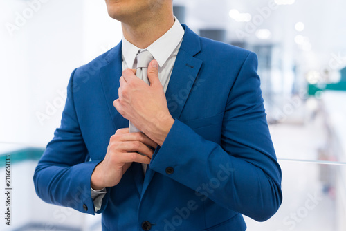 Businessman adjusting his tie - 211665833
