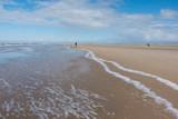 Nordsee endloser Strand mit Wellen und Spaziergängern - 211670255
