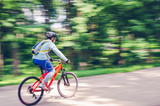 A cyclist in a helmet rides a bicycle path, motion blur - 211670416