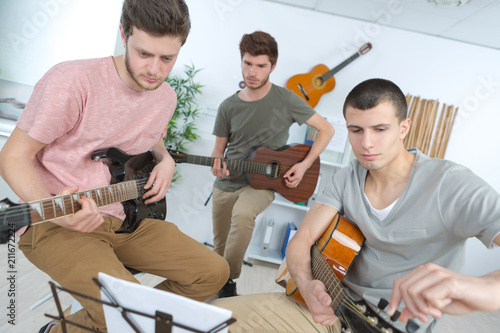 happy young men playing guitar with friends at home - 211672224