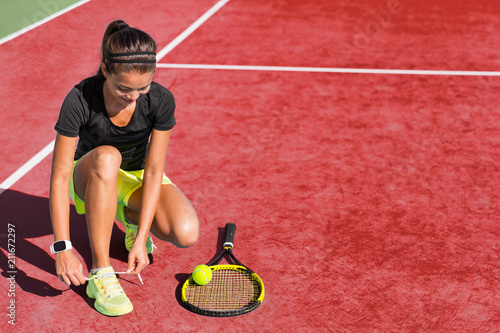 Fotobehang Tennis Sport fitness woman getting ready to play tennis on red clay court tying up shoe laces. Exercise summer training fit girl motivation. Racket and tennis ball on background.