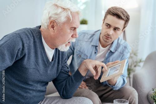 Memory loss. Ill senior man talking and man carrying photo