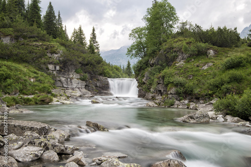 Aluminium Bergrivier waterfall among the pebbles and trees in the mountains
