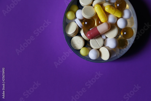 Assorted pharmaceutical medicine pills, tablets and capsules on purple background. Copy space for text - 211678493