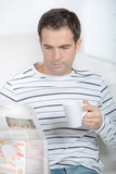 handsome man is reading the newspaper holding a cup - 211681030