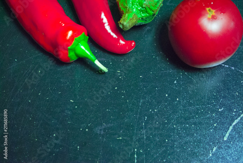 Fotobehang Hot chili peppers vegetables on a black background red pepper tomato aubergine