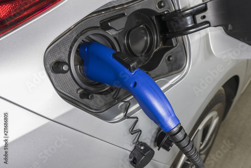Close up of electric vehicle plug charging car inside garage.   - 211686805