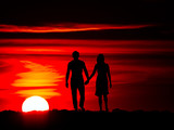 Romantic couple on the sunset with hanging hands - 211692478