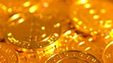 A pile of bitcoin rotating on a shiny golden background - 211697678