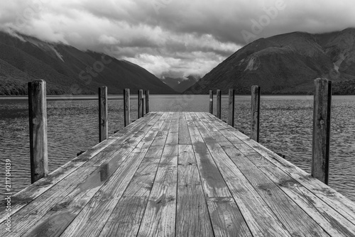 Plexiglas Pier The jetty at Lake Rotoiti, Nelson Lakes National Park, New Zealand, with the lake and mountains in the background. Black and white.