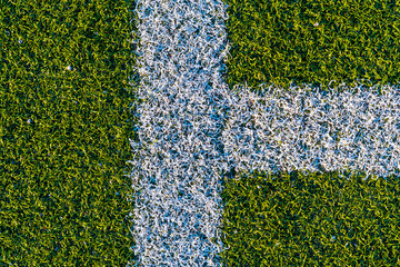 Background from white lines on a green artificial football field