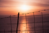 Barbed wire fence with sunset over sea - 211728809