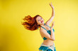 beautiful red-haired woman dancing oriental belly dance in blue suit on yellow background in studio