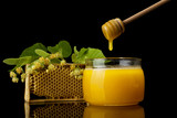 Fresh spring-harvested honey in the jar,next to wooden spoon and frame isolated on black - 211737496