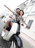 Beautiful young couple is smiling while riding a scooter - 211739488