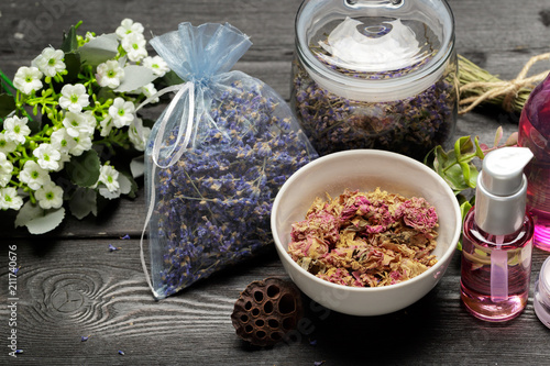 Aromatic composition of lavender, herbs, cosmetics and salt on a dark table top - 211740676