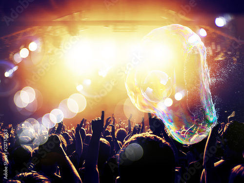 Nightclub with live performance and people clapping under soap bubbles