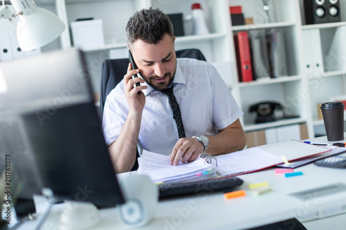 A man is sitting in the office, working with documents and talking on the phone. - 211763078