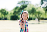 A young happy girl in colorful checkered dress standing in the park, - 211768029