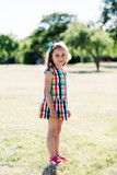 A young happy girl in colorful checkered dress standing in the park, - 211768096