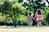 Two little girls running in the park, holding hands. - 211768276