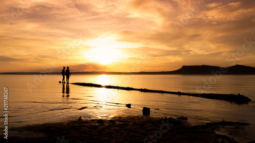 Black silhouette of people walking on a log in the water at a beautiful sunset