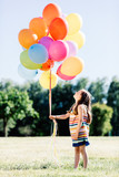 Little girl holding a bunch of colorful balloons in the park. - 211768634